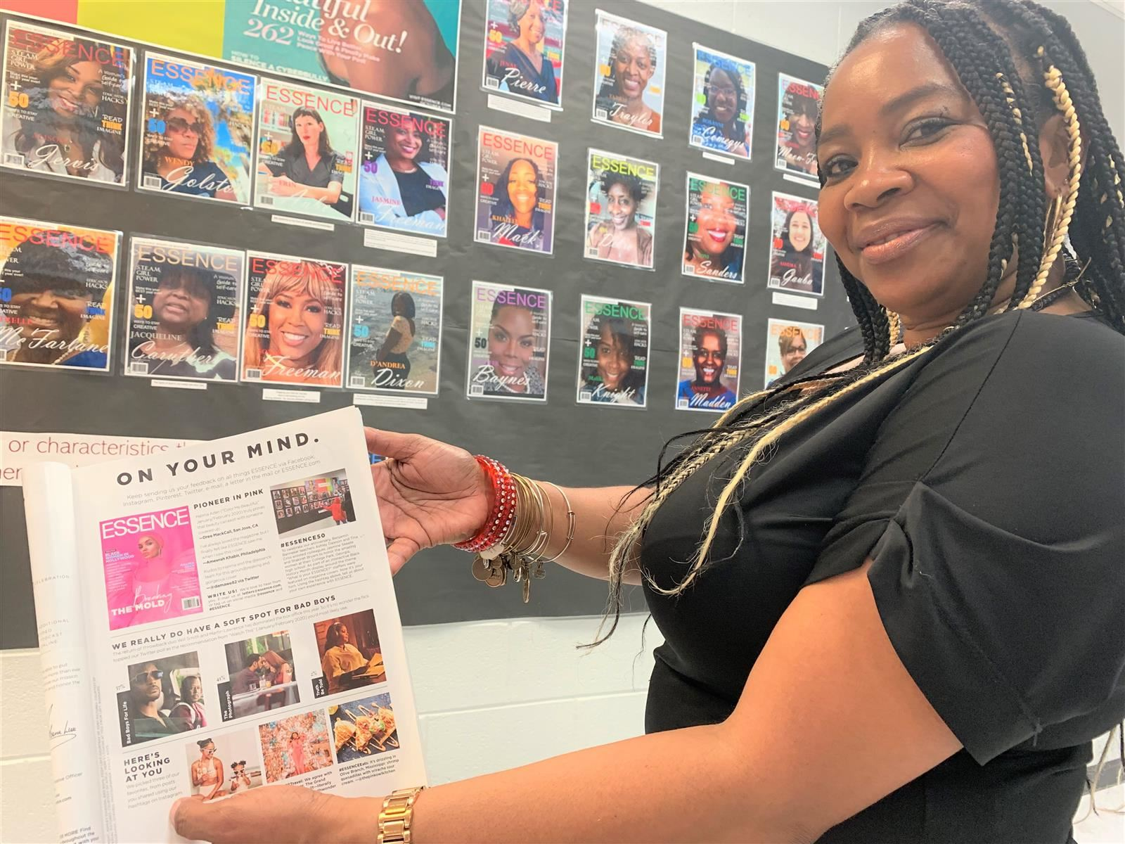 Tina Criss Holds Copy of Essence at Banneker's Essence Wall